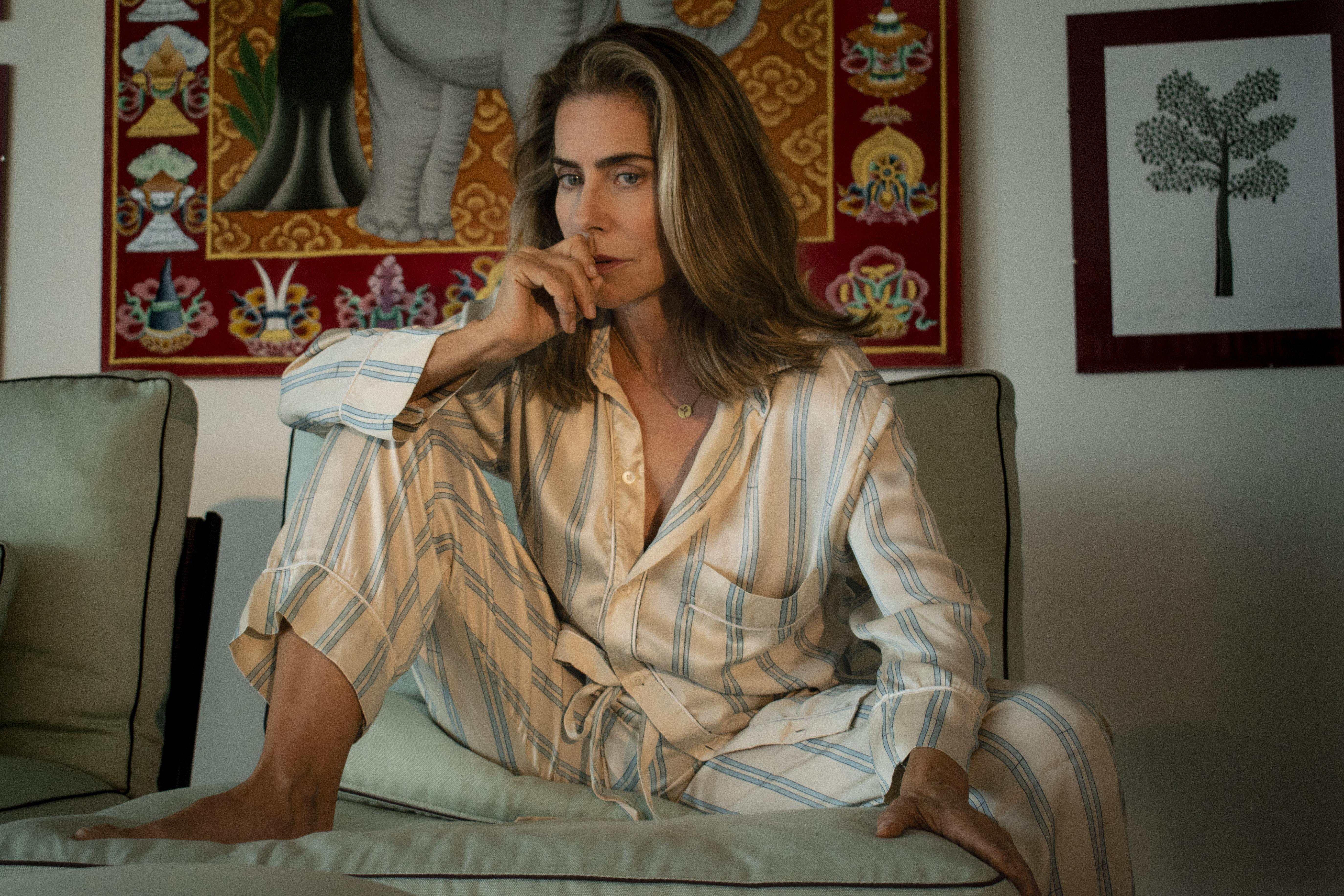 Maite Proença, de pijama, no sofá, com as pernas abertas