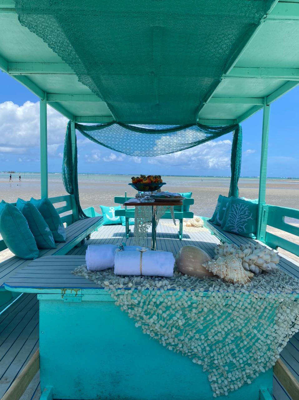A imagem mostra uma mesa posta à beira-mar, com a cor azul predominando