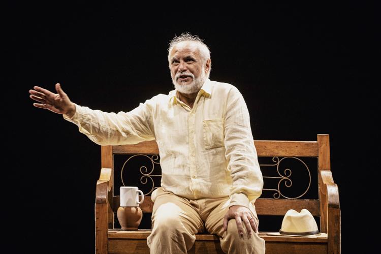O ator Gilson de Barros em um figurino amarelado sentado em um banco com um chapéu e uma cumbuca de água ao seu lado.