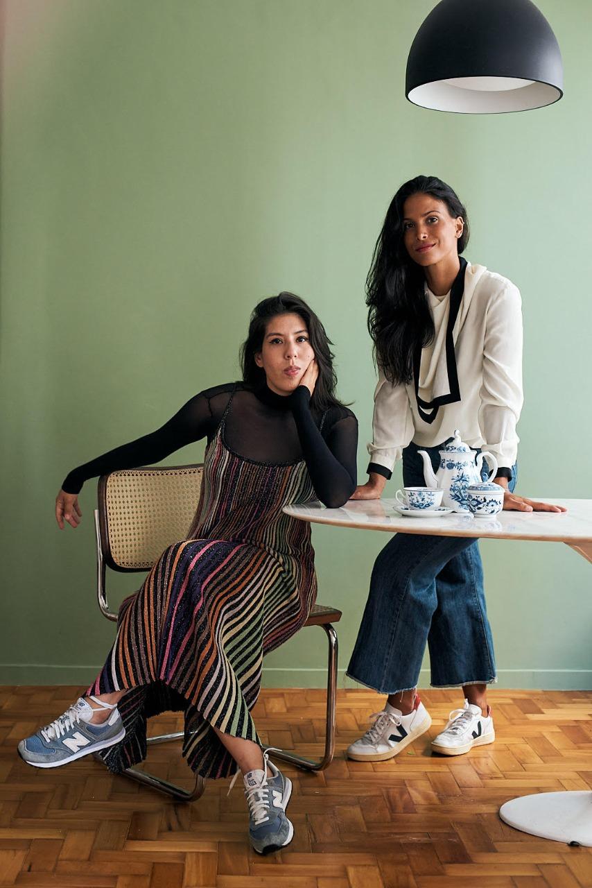 Duas mulheres brancas com cabelos longos castanhos posam na foto, uma em pé com blusa branca, outra sentada com blusa preta