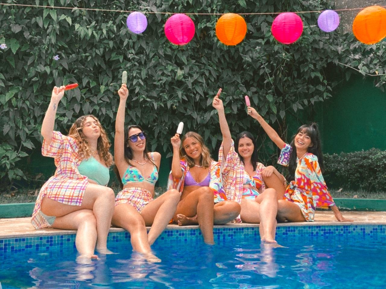 Cinco meninas usando biquini estão sentadas à beira da piscina