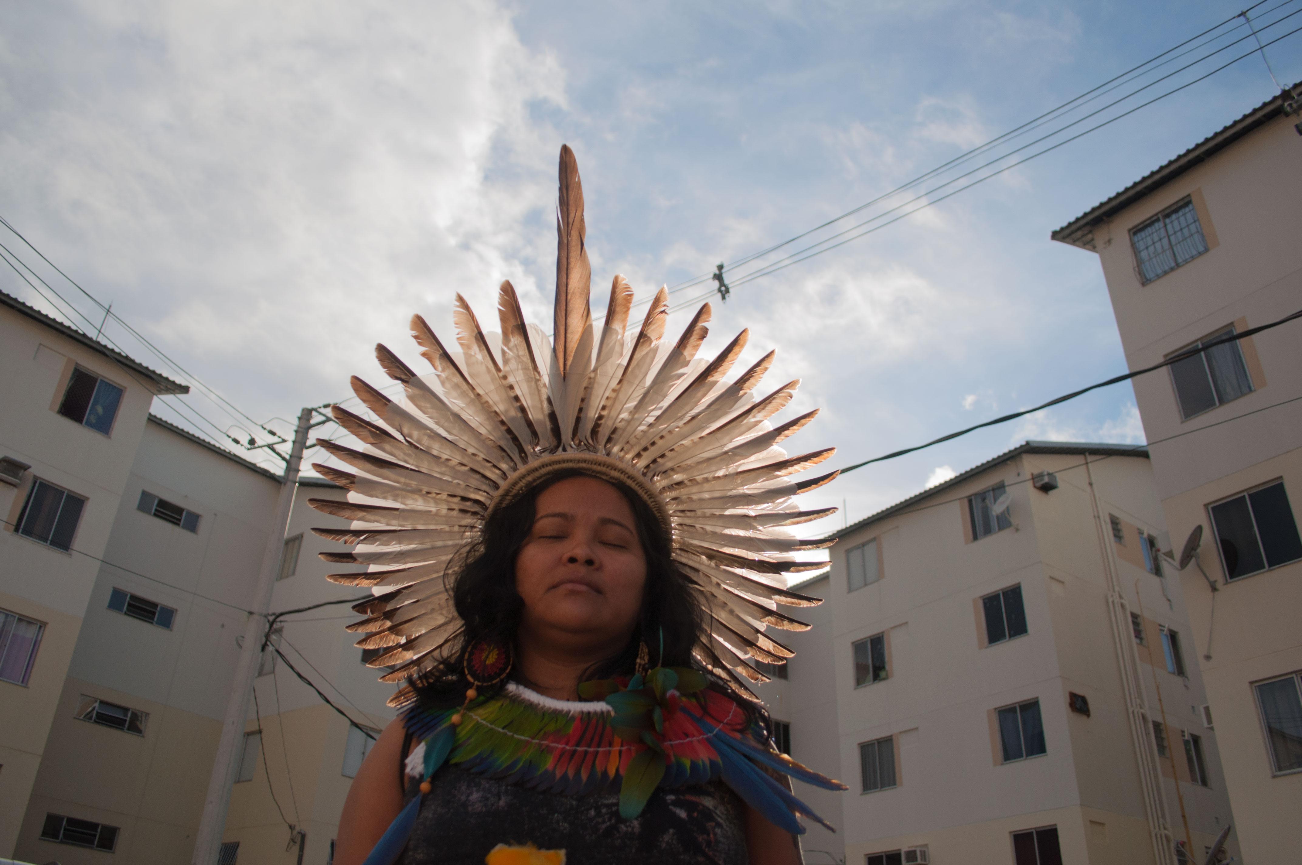Mulher indígena com cocar sob o sol. Atrás dela, um prédio