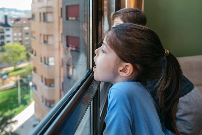 Two children in coronavirus lockdown playing breath on the glass