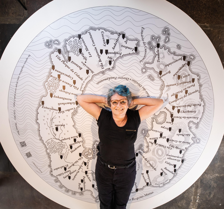 Artista Françoise Schein posa na frente de um de seus painéis, que representa um mapa mundi
