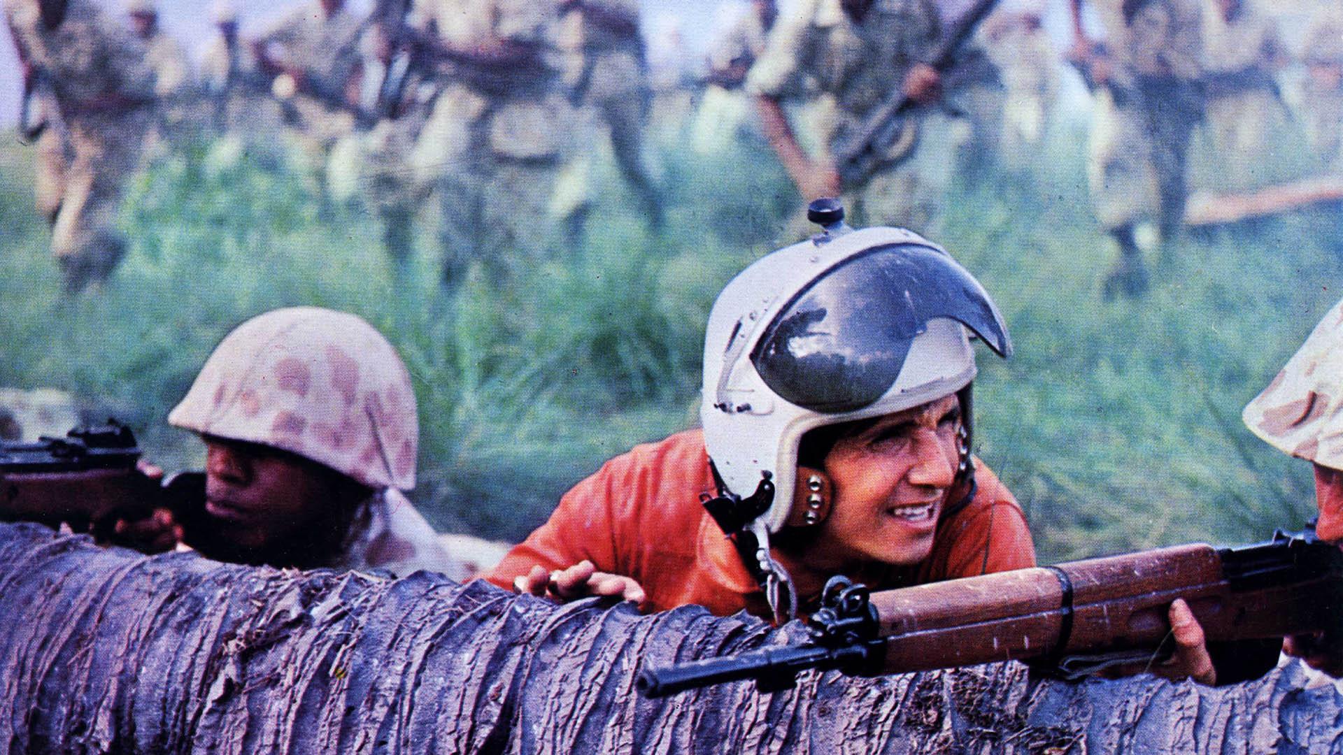 Roberto Carlos jovem, de capacete, abaixado numa trincheira