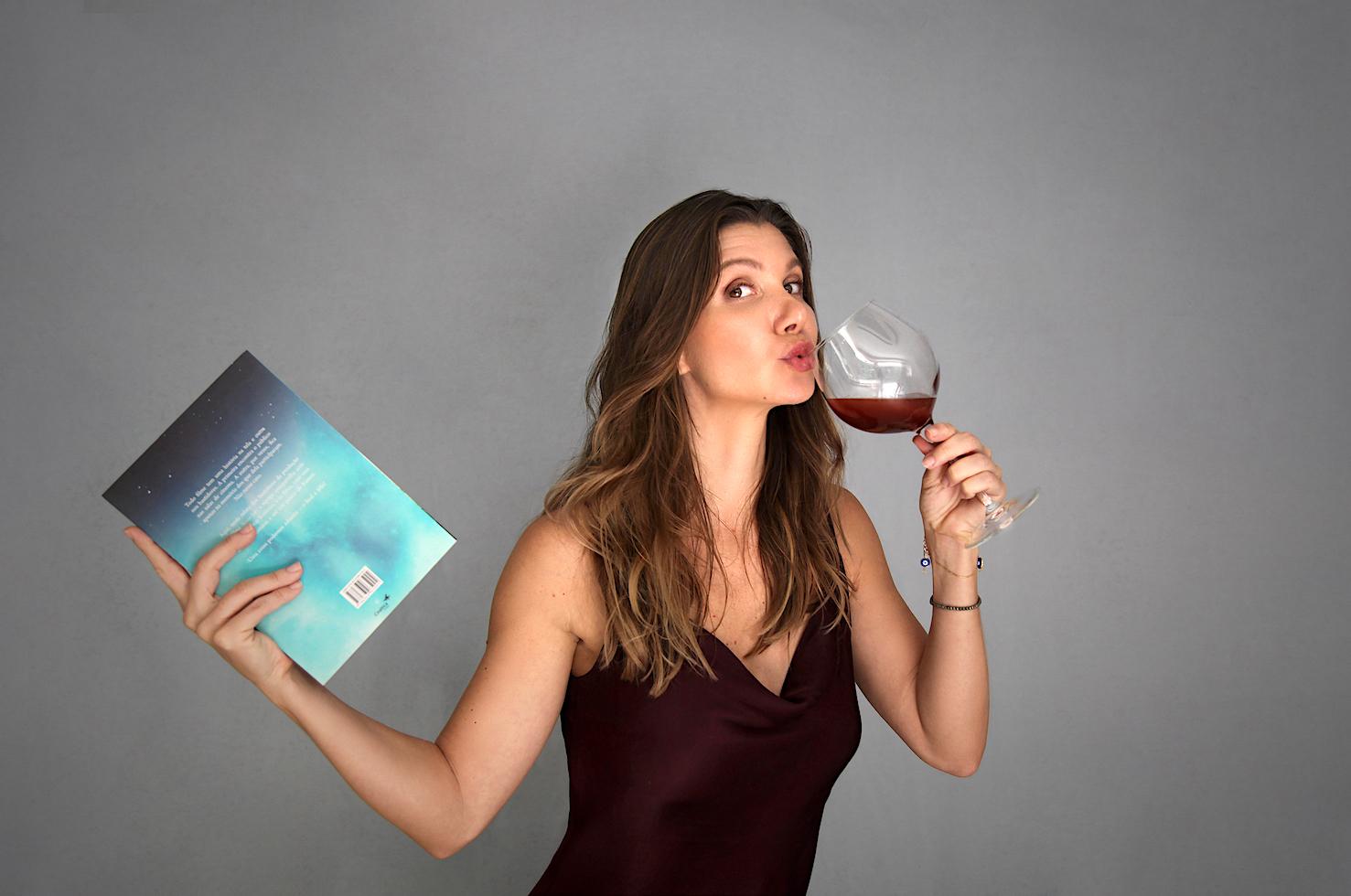 Priscila Assum segurando um livro e uma taça de vinho