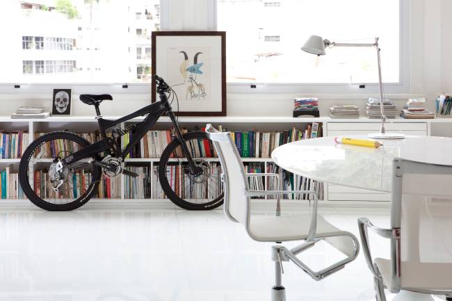 A imagem mostra uma bicicleta apoiada no aparador da sala. No primeiro plano uma mesa com uma cadeira.