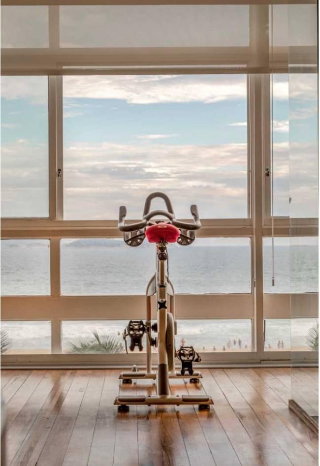 Imagem mostra a bicicleta na sala com vista para o mar.