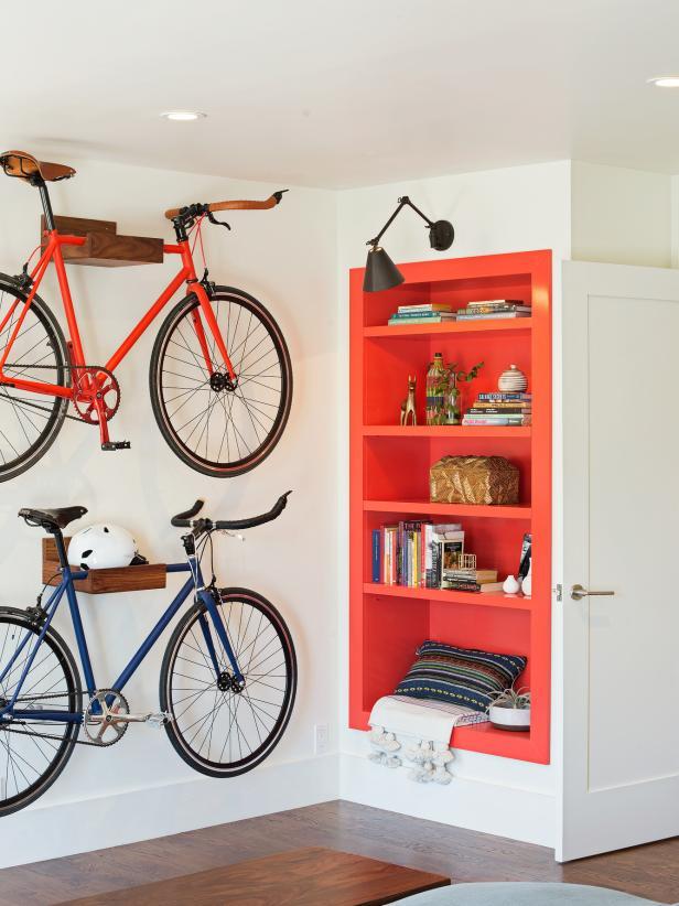 A imagem mostra duas bicicletas na sala penduraras nos nichos.