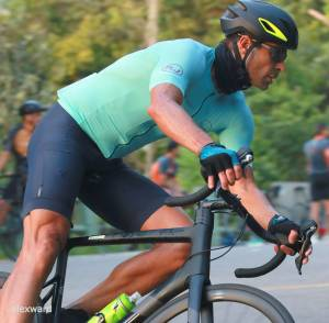 Ciclista faz manobra em pista cercada de verde