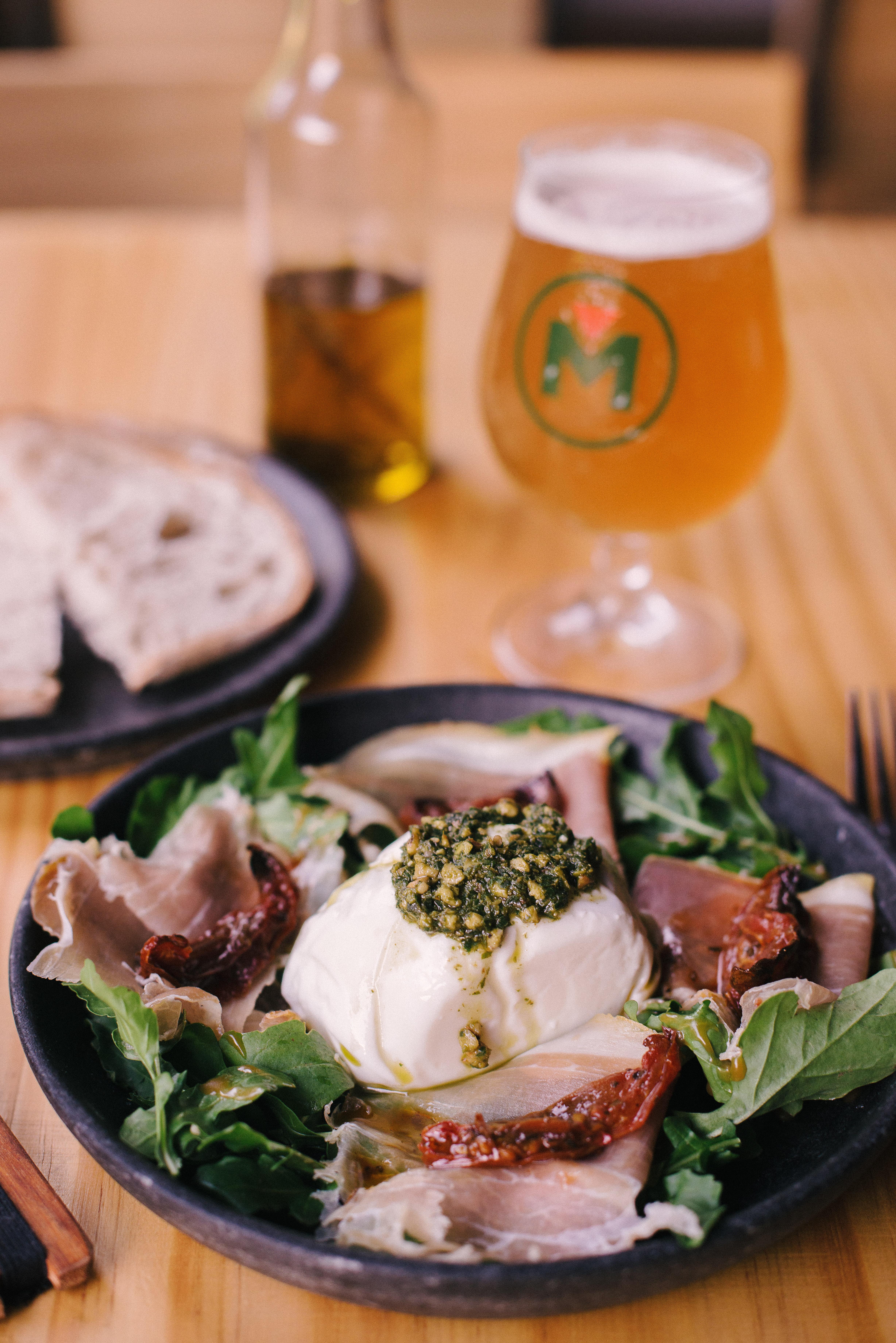A imagem mostra uma salada de presunto cru, burrata e folhas, copo de chope e pão de fermentação natural