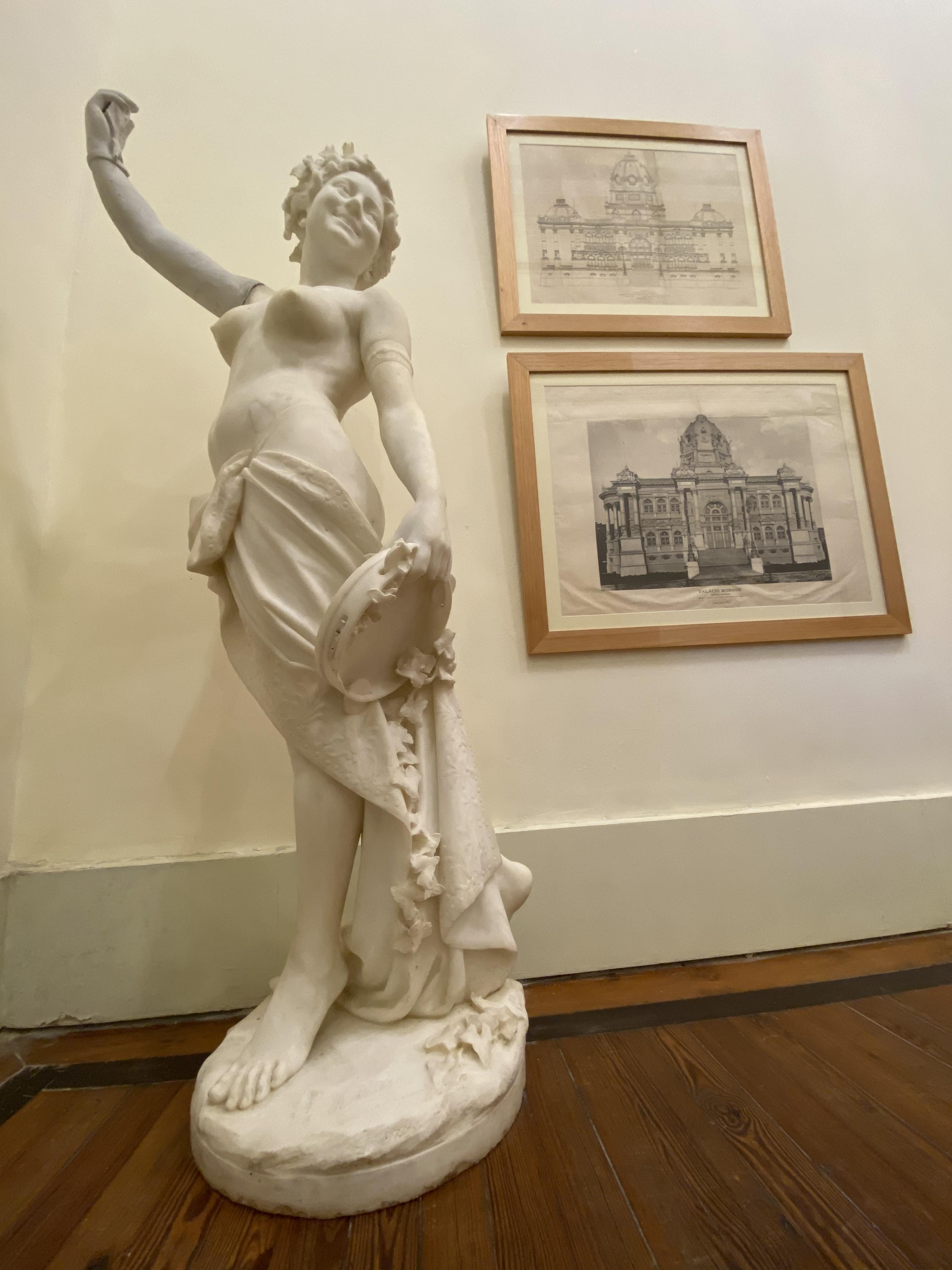 Estátua de mulher com um pandeiro na mão, em mármore