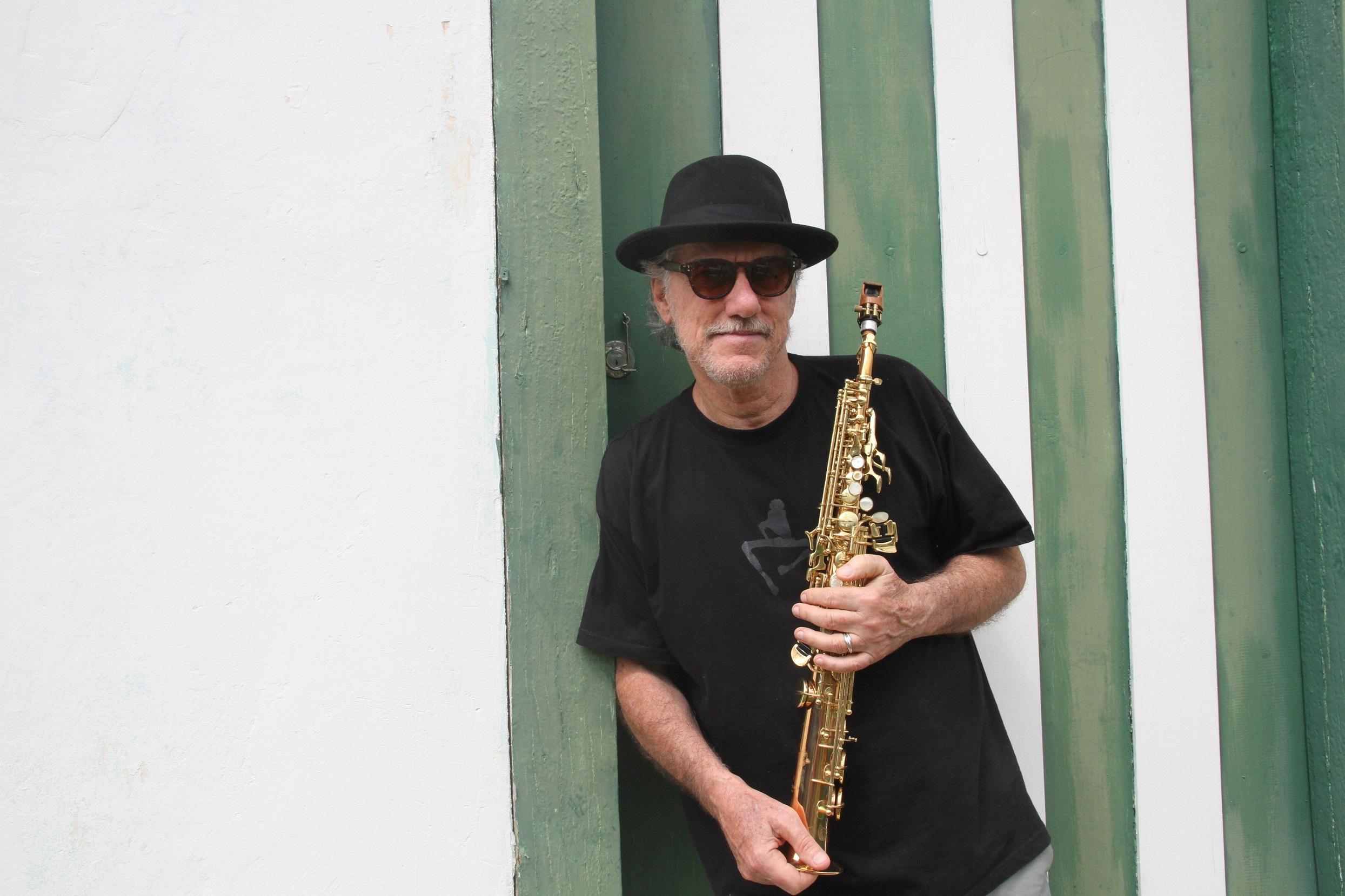 Mauro Senise, encostado numa parede, segurando um clarinete