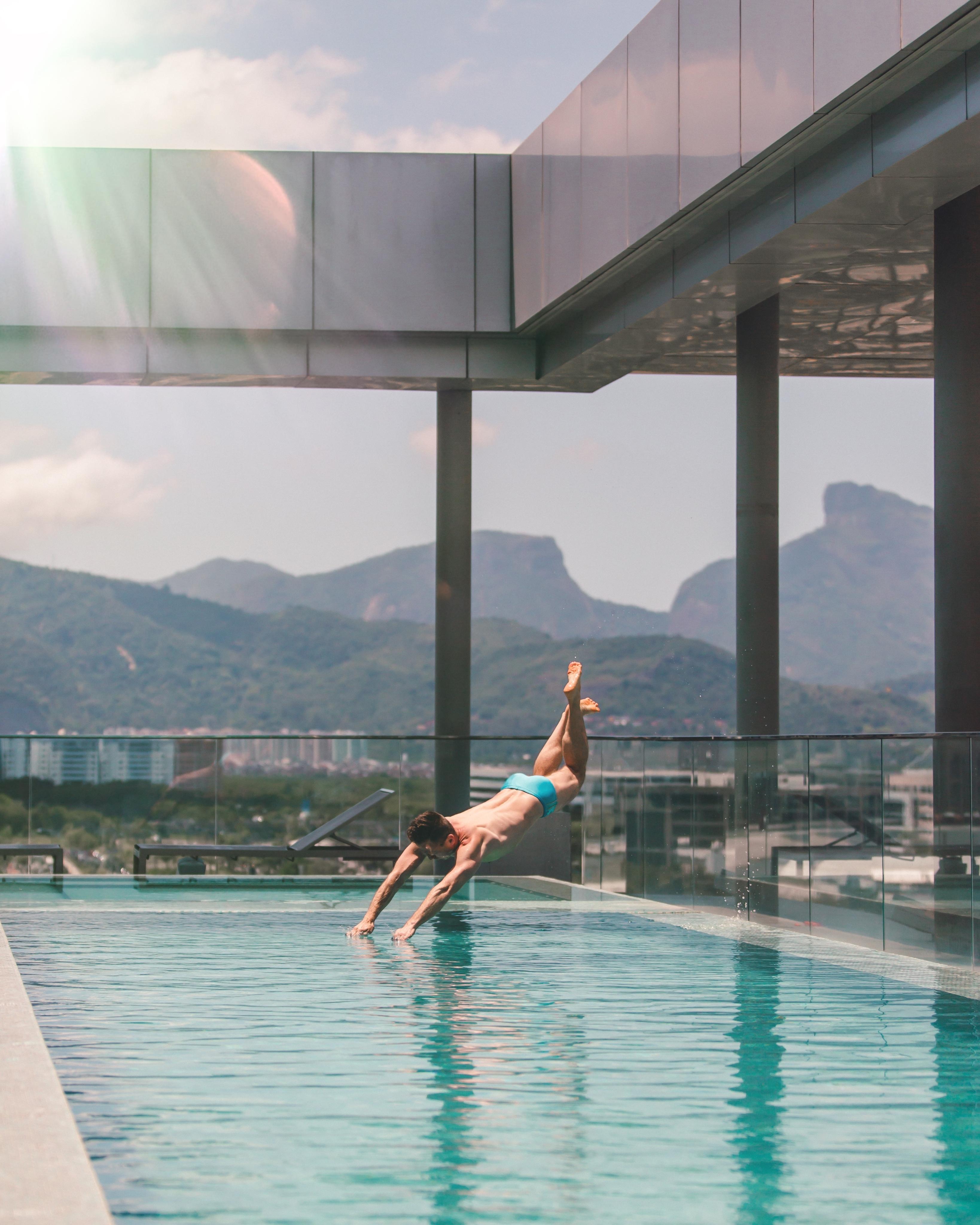 homem mergulha na piscina