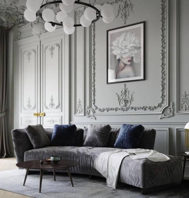 A imagem mostra uma sala de estar com boiserie. Em segundo plano um sofá com almofadas e um lustre no teto.