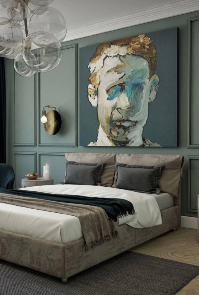 A imagem mostra em primeiro plano uma parede com boiserie e um quadro. Em segundo plano uma cama com um lustre no teto.