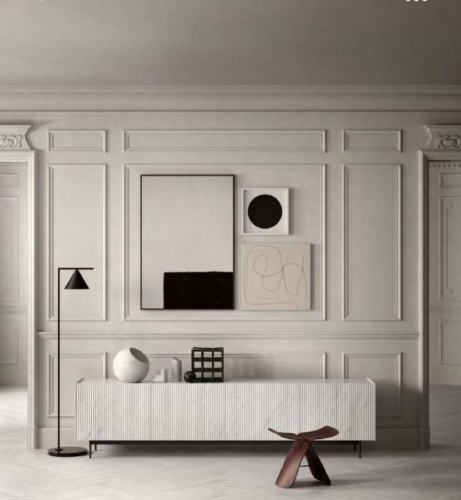 A imagem mostra uma parede com boiserie e quadros. Em segundo plano um aparador e uma luminária de piso.