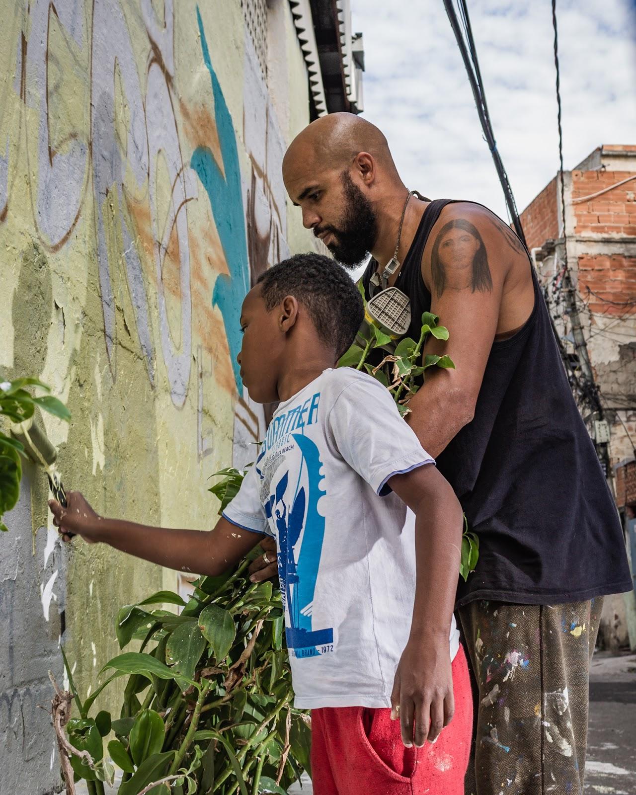 Homem adulto e criança pintam muro