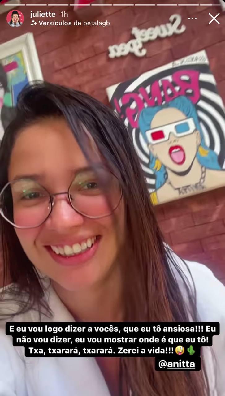 Juliette, de óculos e cabelos molhados, de roupão, com um quadro de Anitta atrás dela