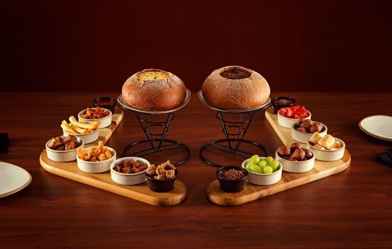 A imagem mostra dois pratos de fondue, um doce, com chocolate e frutas, e outro salgado, com queijos e proteínas