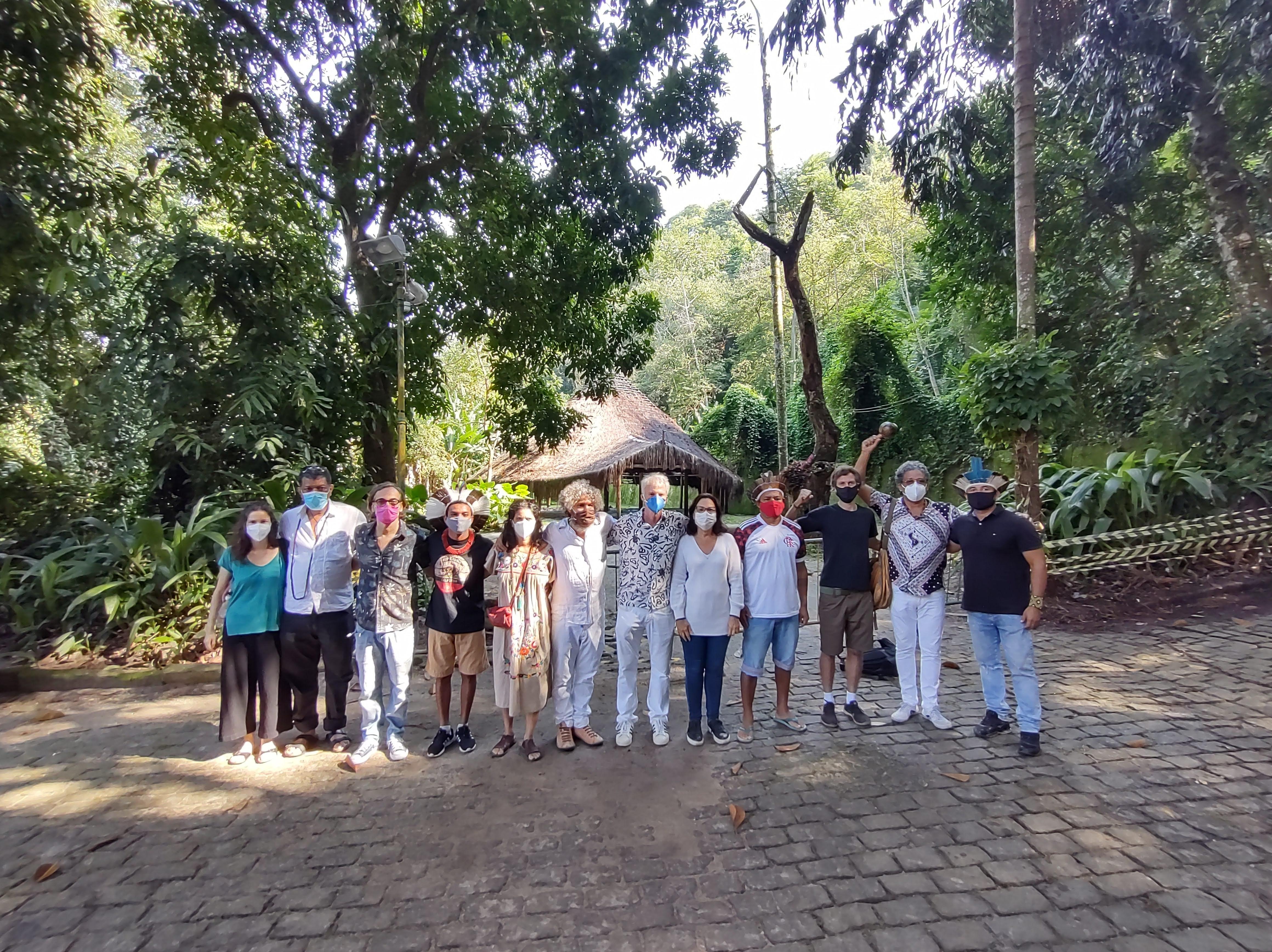 artistas e representantes indígenas em frente à oca do parque lage