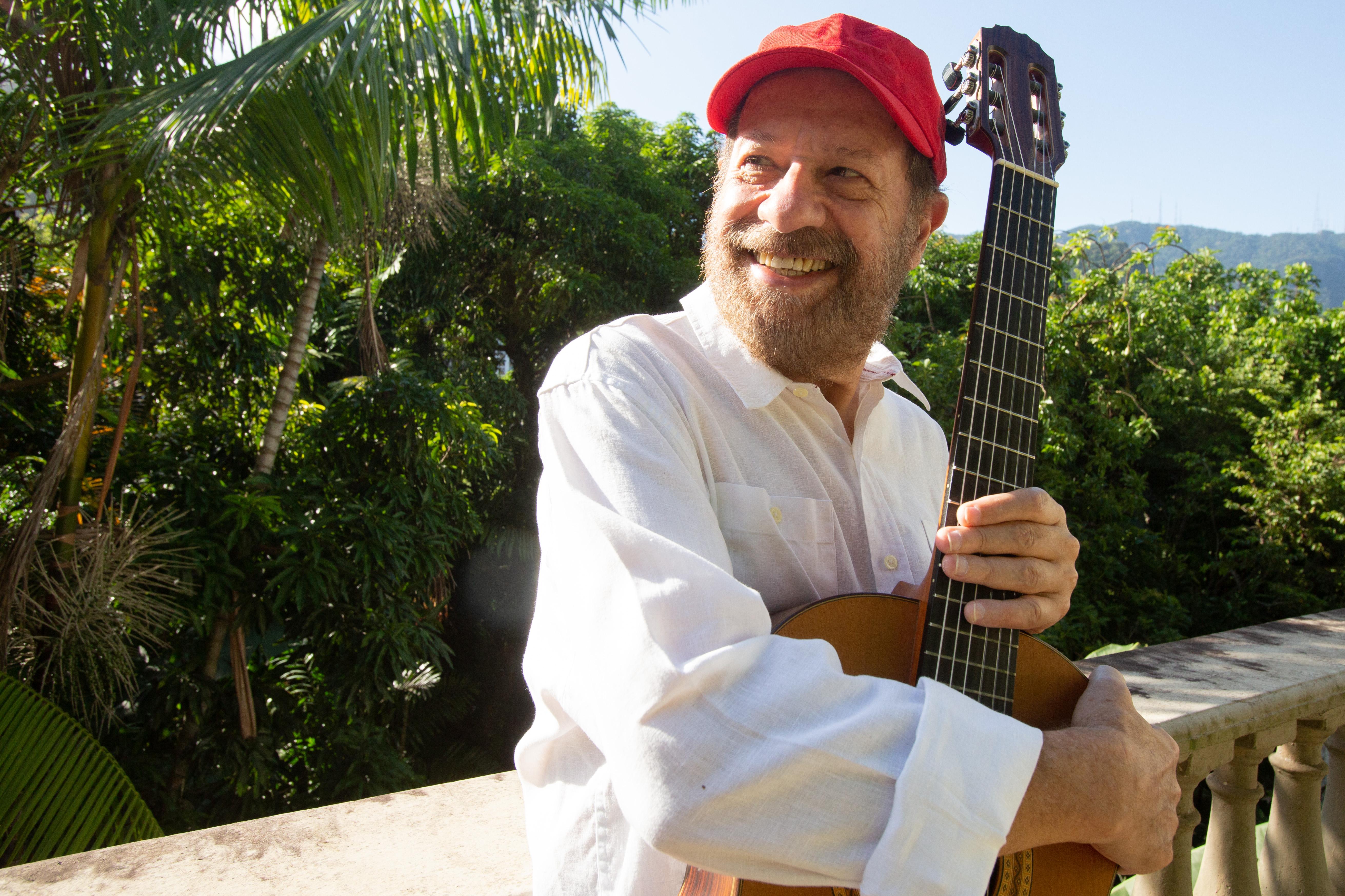 João Bosco de boné, segurando um violão, numa varanda arborizada