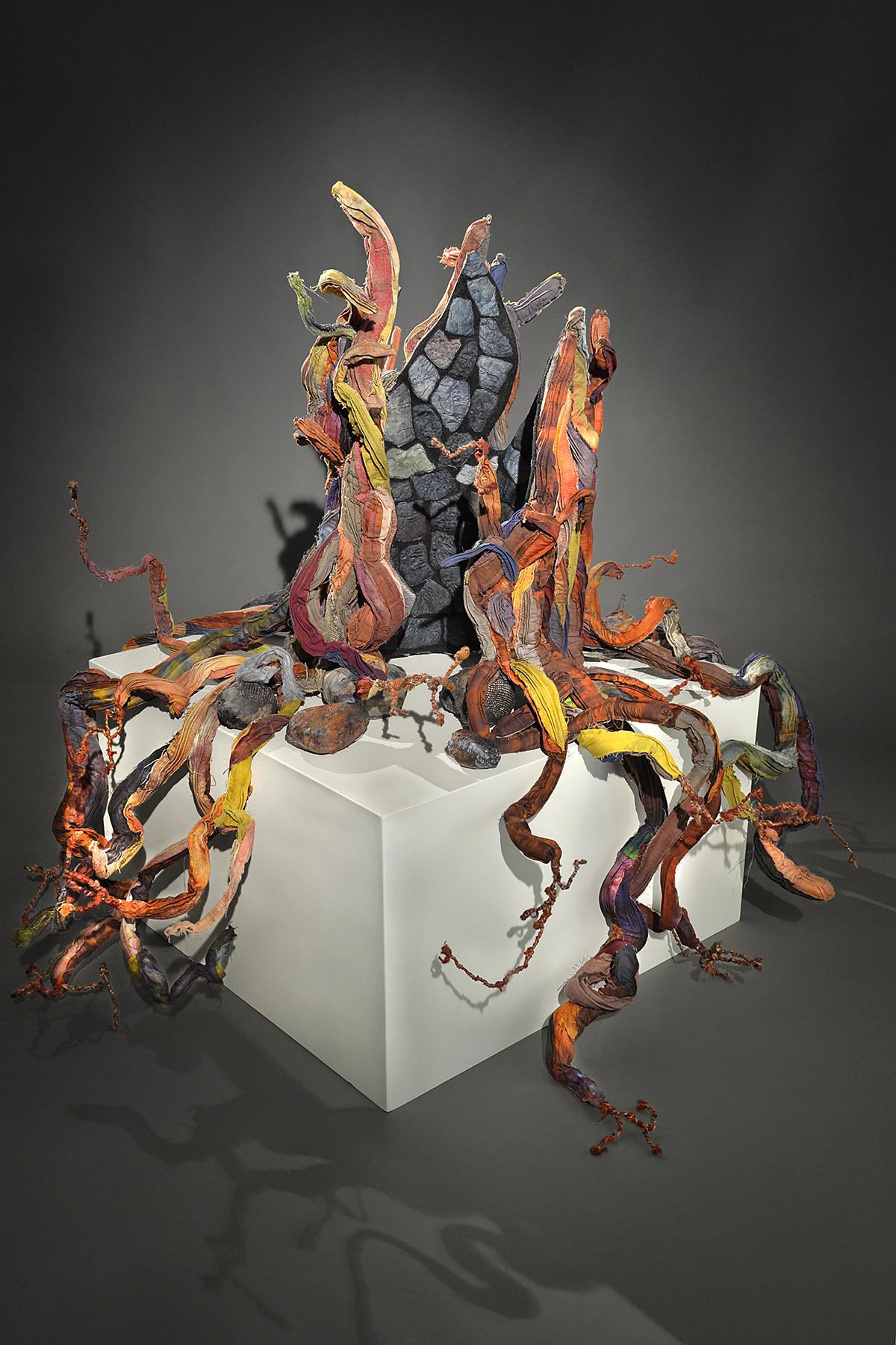 Escultura multicolorida, que lembra tentáculos, sobre um cubo branco