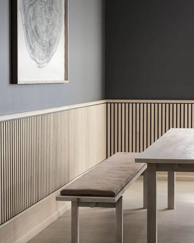 A imagem mostra uma sala com lambri na parede. Em segundo plano um banco e uma mesa.
