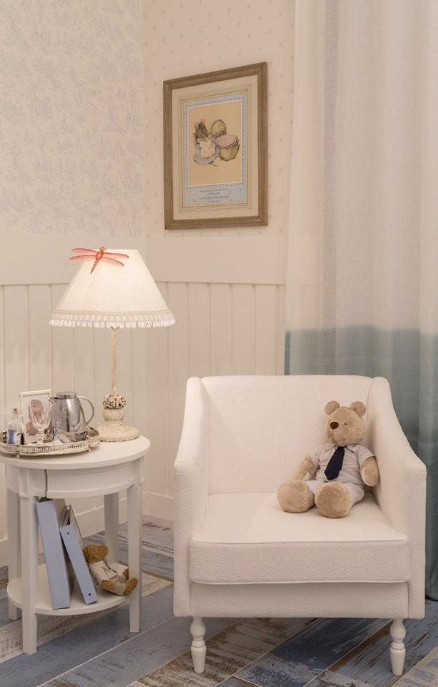 A imagem mostra um quarto de criança. Em primeiro plano uma parede com lambri, Em segundo plano uma poltrona e ao lado uma mesinha lateral.