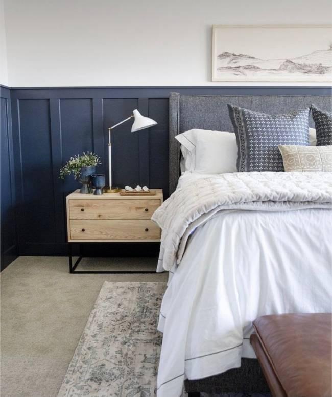 A imagem mostra um quarto de dormir com lambri. Em segundo plano uma mesinha de cabeceira e a cama.