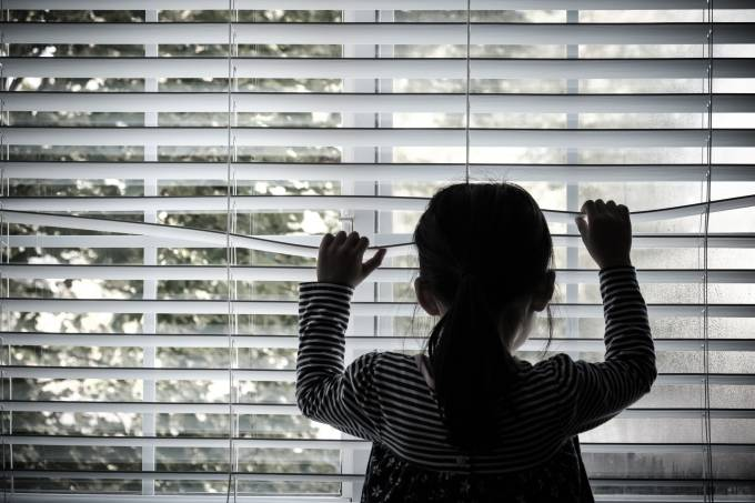 Lonely little kid in front of a window
