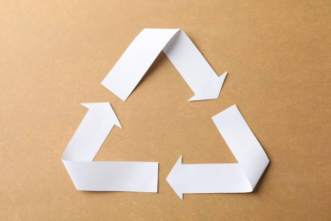 Recycling sign on craft background, top view