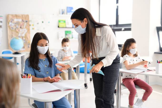 Teacher and children with face mask back at school, disinfecting hands.