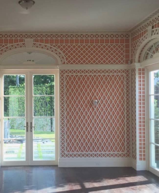 Imagem mostra uma sala vazia com uma parede salmão toda revestida de treliça branca