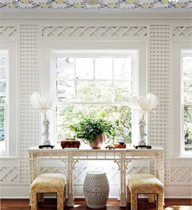 Imagem mostra uma sala com parede branca toda revestida de treliça. Em segundo plano um aparador com objetos de decoração.