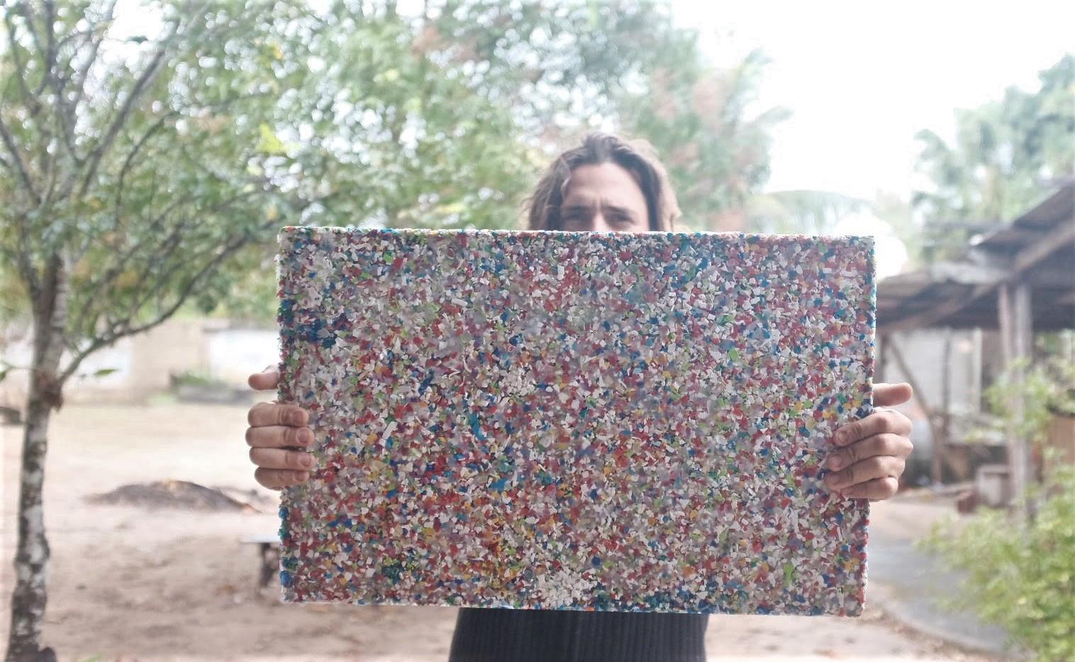 Homem segura placa com pedaços de plástico triturados e prensados
