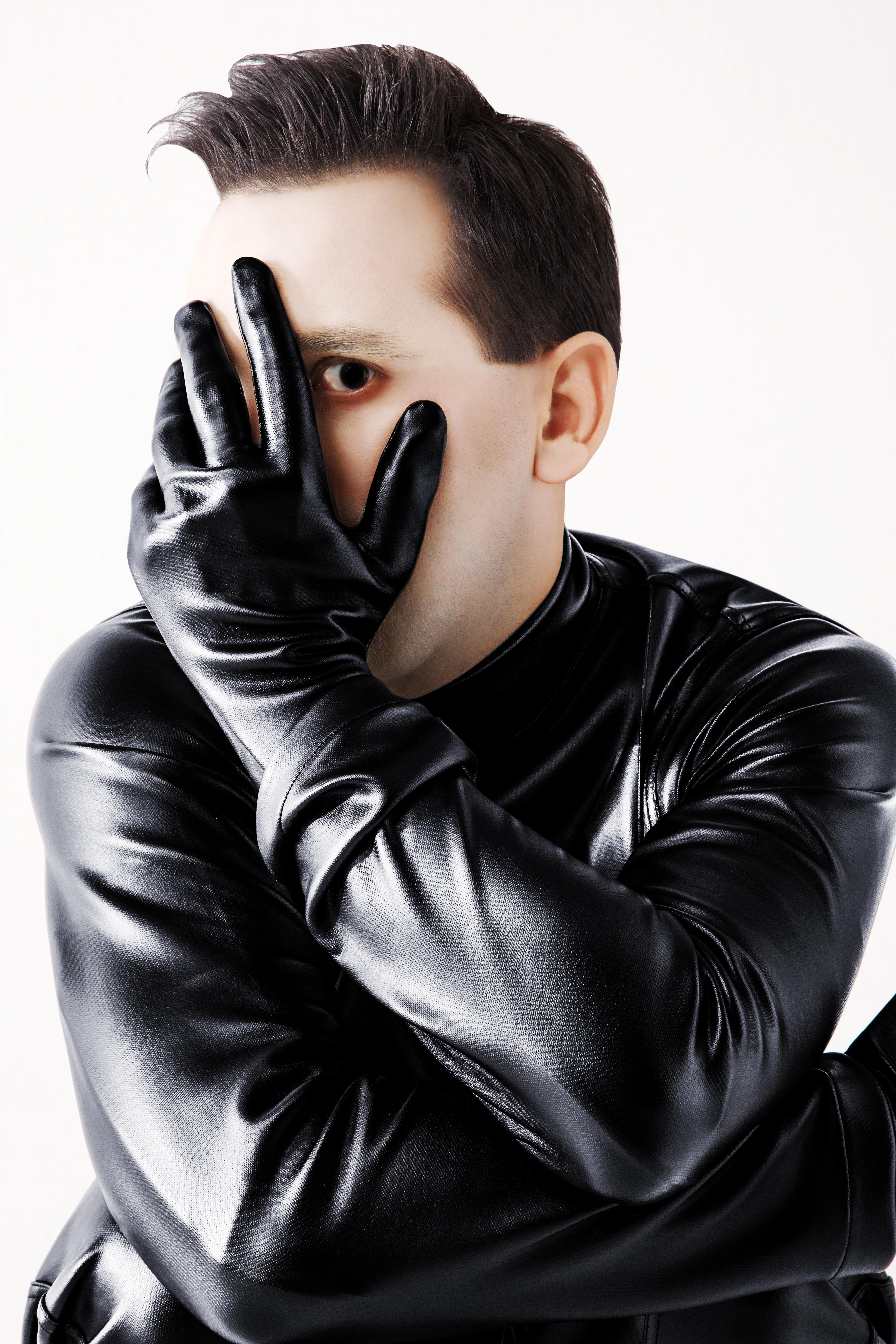 Homem com roupa de couro preta com uma das mãos, de luva preta, no rosto