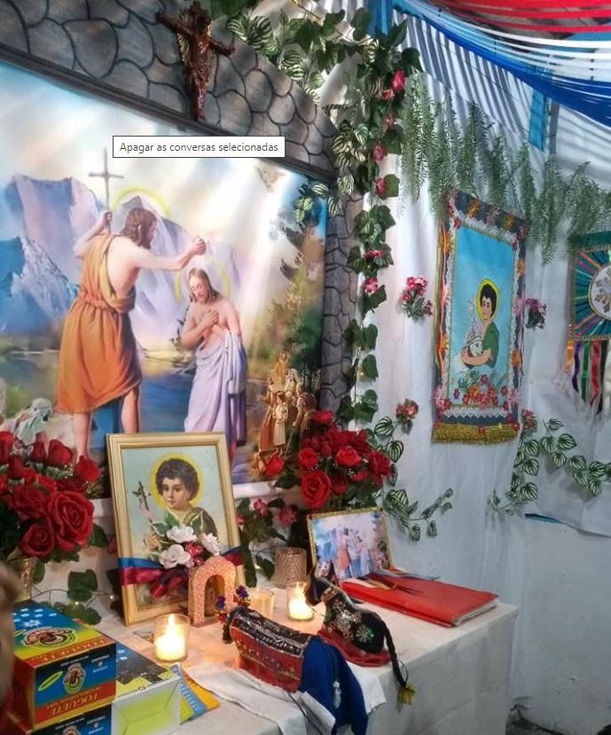 Foto do Altar do Boi Brilhante de Lucas onde aparecem Santo Antônio, velas e flores