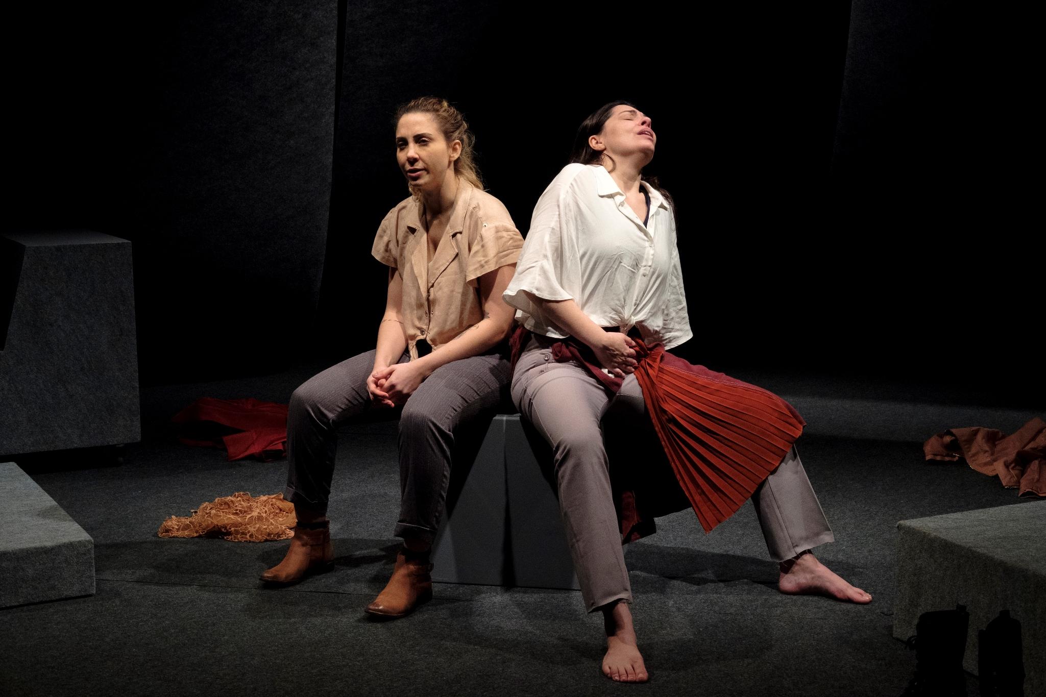 Atrizes Carol Cezar e Fernanda Heras no palco, sentadas em cubo