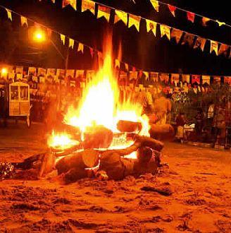 Uma grande fogueira de São João pegando fogo entre várias bandeirinhas de Festa Junina