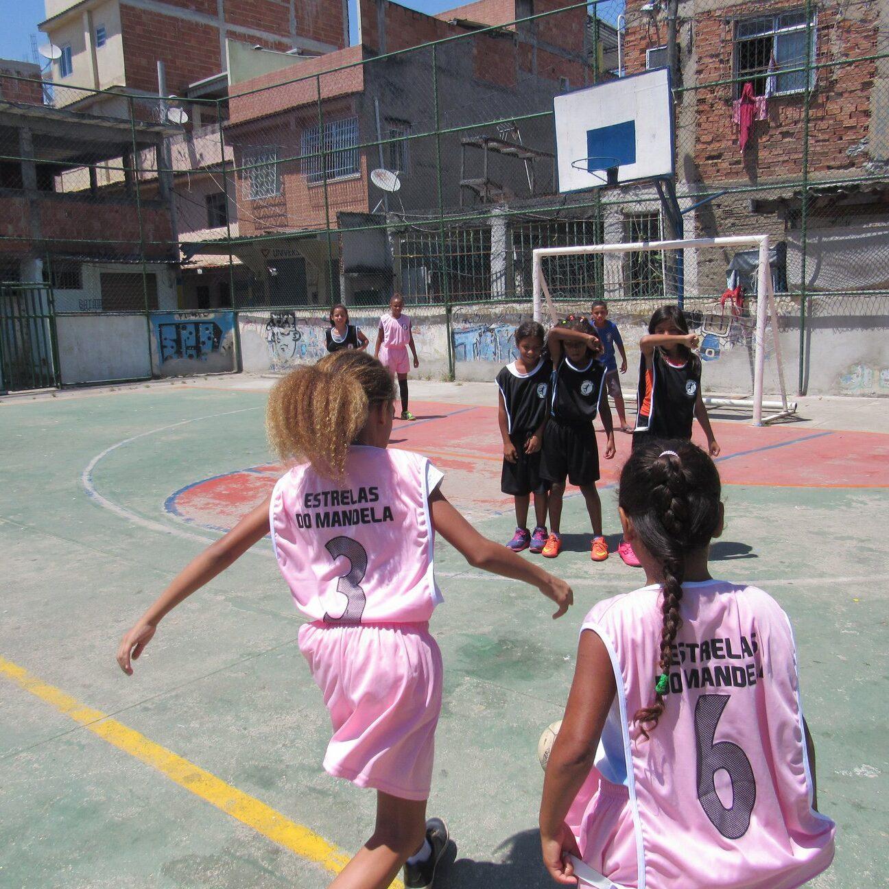 Imagem mostra meninas com uniforme rosa claro jogando futebol em uma quadra da comunidade