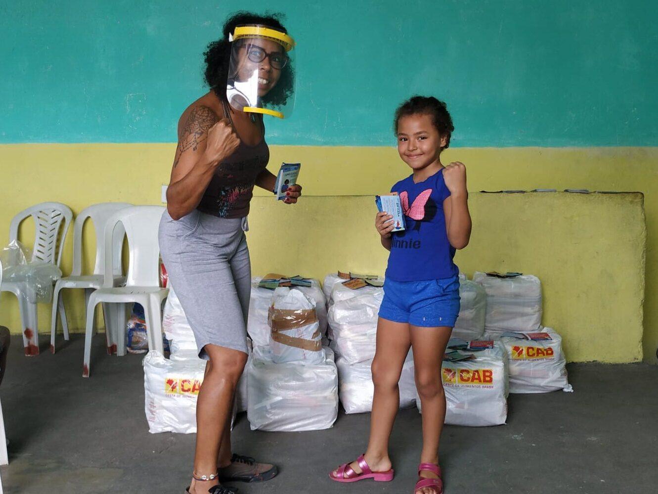 Imagem mostra uma mulher e uma menina em frente a cestas básicas