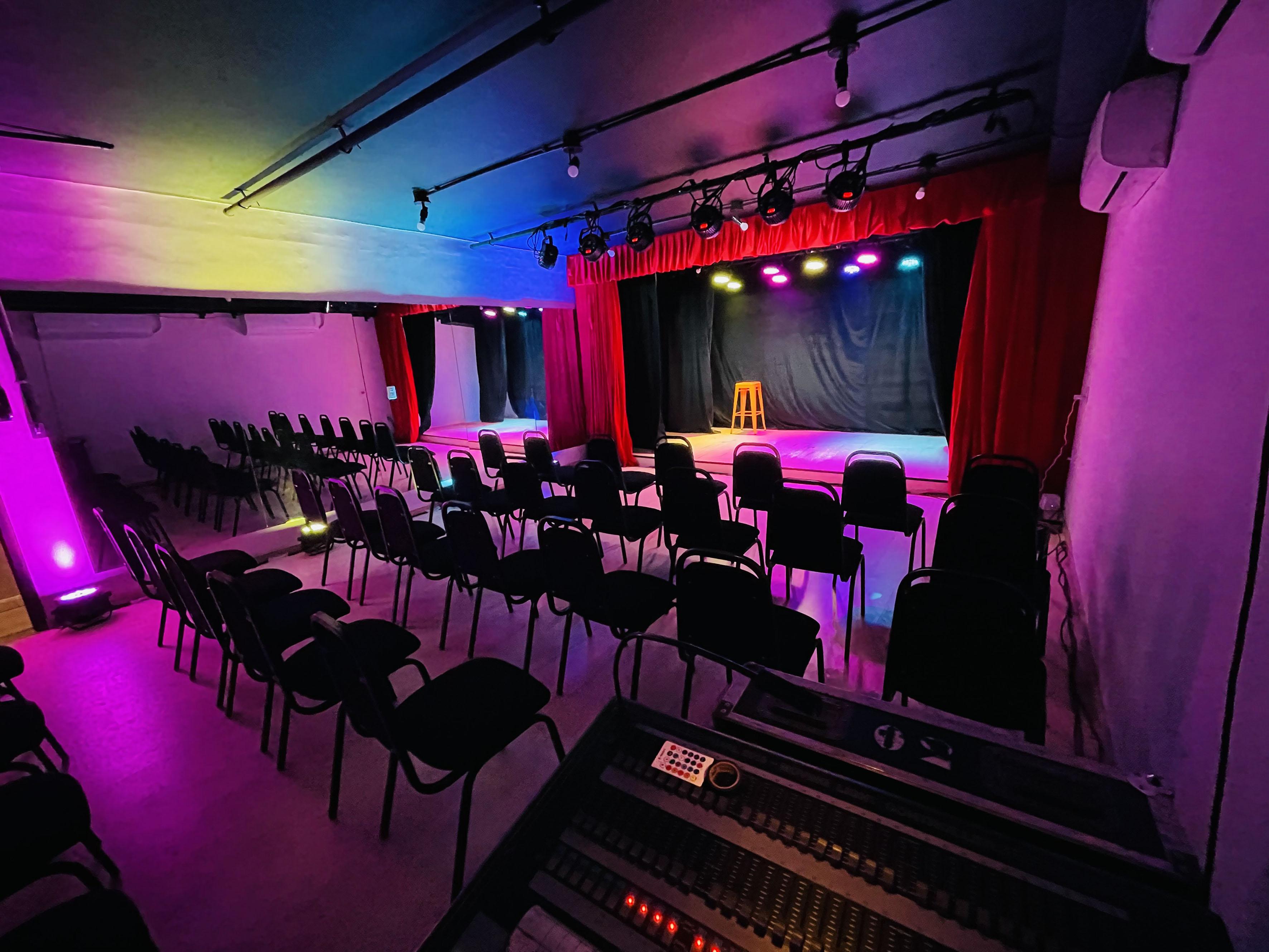 Sala de teatro com luzes na ribalta e uma mesa de som à direita