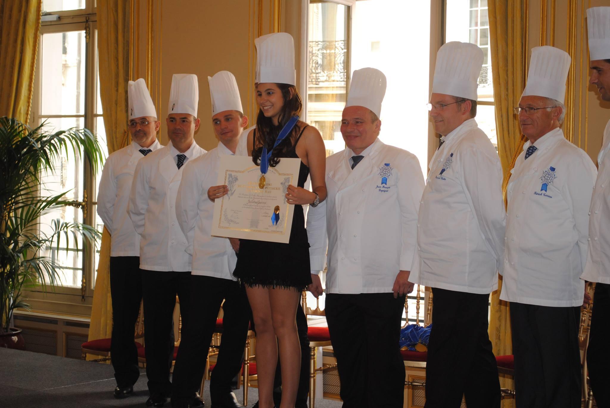 Moça jovem com vestido preto posa com diploma e chapéu branco de chef de cozinha. Ao seu lado, estão outros chefs usando chapéu e uniforme branco