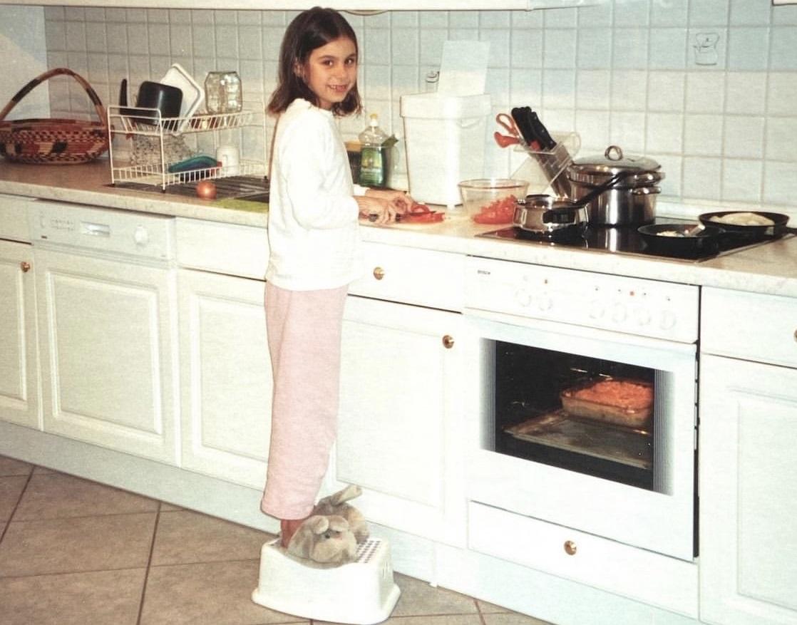 Foto mostra menina cozinhando em cima de um banquinho branco