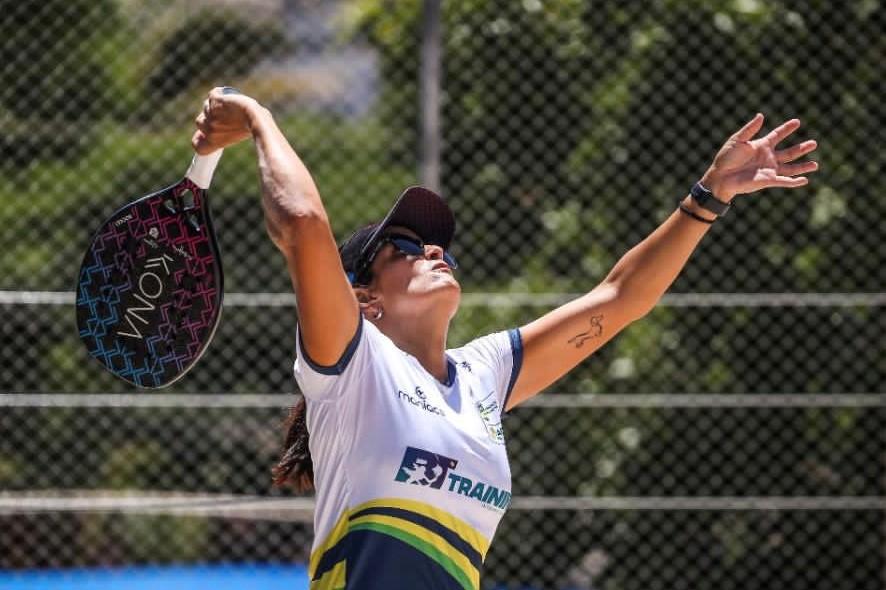 Foto mostra jogadora praticando tênis na praia