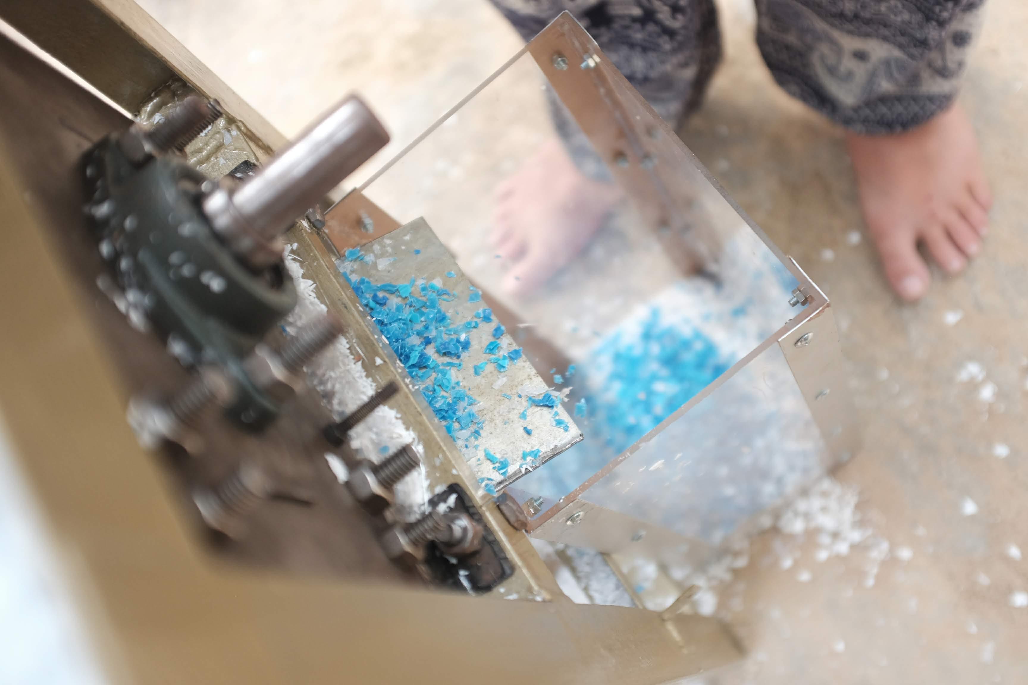 Imagem mostra plástico azul triturado em pequenos pedaços