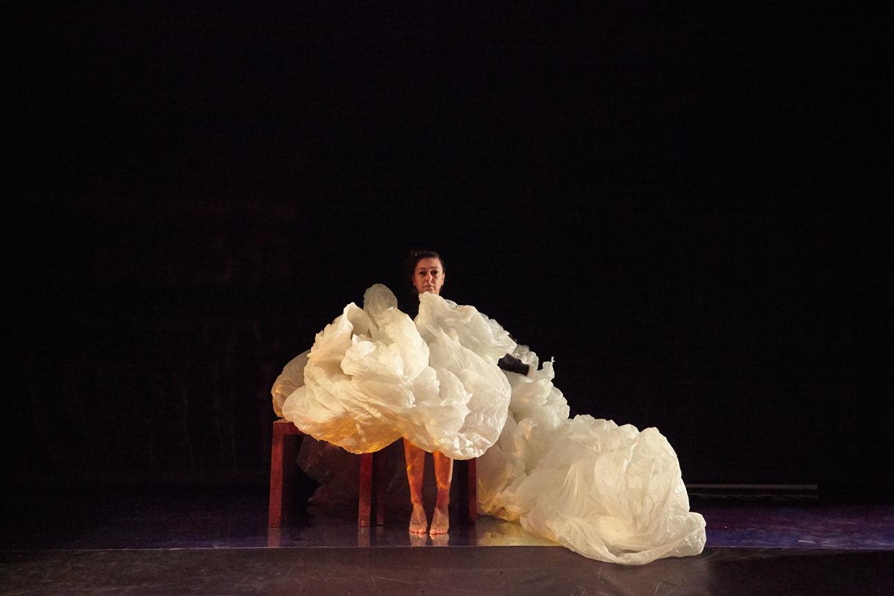 Atriz no palco com um grande tecido em volta dela