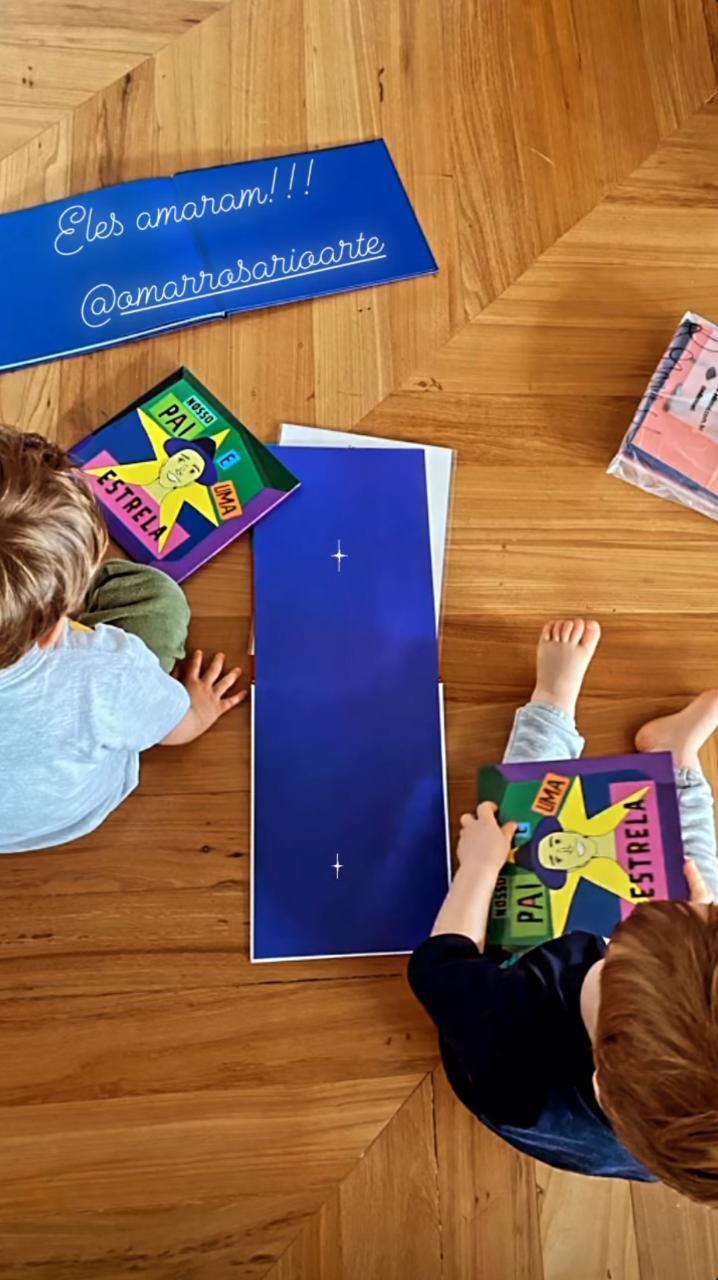 Imagem mostra duas crianças penas segurando dois livros infantis, sentadas em um chão de madeira