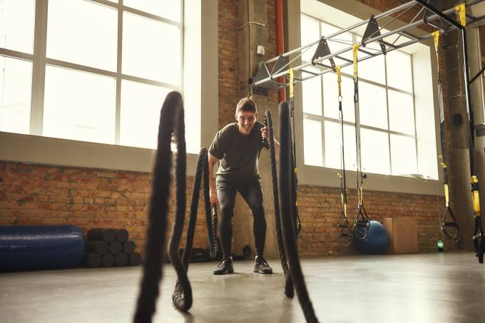 Battle ropes exercises. Young and strong man doing CrossFit exercises with a rope at gym